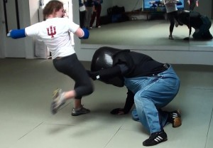 Model Mugging student delivers a knee to the head of the padded assaialant